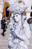 VENICE, ITALY - FEBRUARY 27, 2014: Carnival of Venice. Person in white costume with rose in St. Mark`s Square during Carnival of Venice stock image