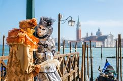 VENICE, ITALY - FEBRUARY 27, 2014: Carnival of Venice. Two people in beautiful carnival costumes in background blue lagoon of Venice and gondola stock images