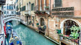Venice, Italy - February 17, 2015:  Classical picture of the venetian canals with gondola across the canal. Stock Images