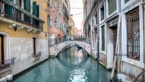 Venice, Italy - February 17, 2015:  Classical picture of the venetian canals with gondola across the canal. Royalty Free Stock Image