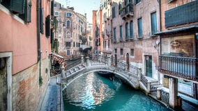 Venice, Italy - February 17, 2015:  Classical picture of the venetian canals with gondola across the canal. Stock Photography
