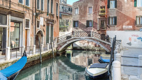 Venice, Italy - February 17, 2015:  Classical picture of the venetian canals with gondola across the canal. Royalty Free Stock Images