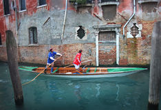 Gondola race in Venice as a canoe. Venice, Italy - 27 February, 2009: fun canoe race in Venice during the Carnival season, two men rowing along the canals in Royalty Free Stock Image