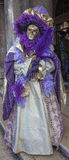 Venetian Disguise. Venice, Italy-February 18, 2012: Image of a person disguised in a complex purple costume during the Venice carnival days Royalty Free Stock Photos