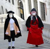 Venice, Italy - February 5, 2018: masked lovers walk on the step. Venice, Italy - February 5, 2018: a couple of masked lovers walk on the steps of the famous Stock Image