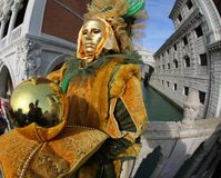 Venice, Italy - February 5, 2018: person in costume with golden. Mask near the famous bridge called Ponte dei Sospiri in Italian Language and a big gold sphere Royalty Free Stock Images
