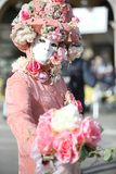 Venice, Italy - February 5, 2018: person with pink carnival mask. Venice, Italy - February 5, 2018: person in costume with carnival mask and a big bouquet of Stock Image