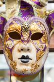 A Carnivale Mask. Venice, Italy - February 28, 2015: A purple and gold Carnivale Mask hangs in a store window in Venice, Italy royalty free stock photography