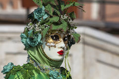 Green Disguise. Venice, Italy- February 18th, 2012:Environmental portrait of a person in sophisticated green Venetian costume posing in Sestiere Castello during stock image