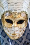 A Carnivale Mask. Venice, Italy - February 28, 2015: A white and gold Carnivale Mask hangs in a store window in Venice, Italy royalty free stock photo