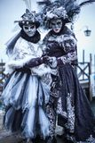 Omen with colorful Venetian costume and mask. VENICE, ITALY - FEBRUARY 7, 2018: Women with colorful Venetian costume and mask in front of gondolas in Piazza San stock photo