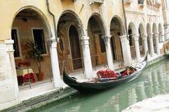Venice,Italy, a gondola on Rio di San Felice. Venice, Italy, a characteristic venetian gondola, on the Rio di San Felice, and porch with arches and columns Stock Image