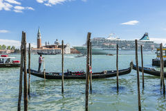 Venice in Italy , Gondolas with big shop in background Royalty Free Stock Images