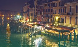 VENICE, ITALY - 02.23.2019: Gondolas moored on Grand Canal in Venice. Tourists in cozy restaurants outdoors. Grand Canal at night, royalty free stock images