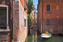 Venice, Italy, historic tenements and boat. Venecian street canal lit with old houses and boat Stock Photos