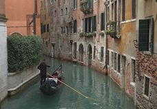 Gondola with tourists on a narrow canal surrounded by old buildings in Venice stock image