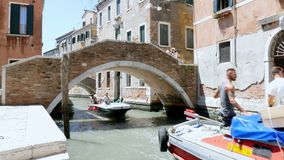 VENICE, ITALY - JULY 7, 2018: along a narrow canal, under a bridge, cargo boats are passing, delivering all that is
