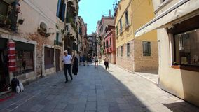 4K. Tourists walking through an old street in Venice, Italy. Subjective shot. Venice, Italy-27 July, 2018: 4K. Tourists walking through an old street in Venice stock video footage