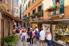 Narrow street with typical shops and restaurants in Venice. VENICE,ITALY - JULY 26,2017 : Narrow street with typical shops and restaurants in Venice Royalty Free Stock Photos