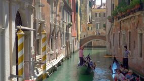 Gondoliers at narrow canal in Venice stock footage