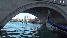 Gondolas under low bridge in Venice stock video