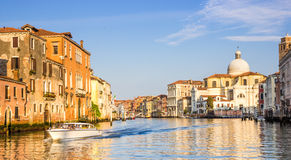 Venice, Italy - June 28, 2014: Cityscape of Venice - motorboat sailing on Grand Canal past colorful buildings. Venice cityscape - motorboat sailing on Grand royalty free stock image