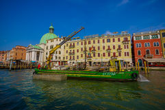 VENICE, ITALY - JUNE 18, 2015: Equipment with crane in Venice canals, machinery to help boats, behind green dome.  Royalty Free Stock Image
