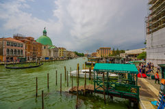 VENICE, ITALY - JUNE 18, 2015: Goldola port for turists in Venetian canal, water runs all around the city. Green dome. View stock images
