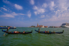 VENICE, ITALY - JUNE 18, 2015: Gondola ride on Adriatic sea, people looking Venice on the side and a big cruise arriving Royalty Free Stock Photos