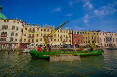 VENICE, ITALY - JUNE 18, 2015: Green boat with a crane parking in Venice canals, equipment to help.  Royalty Free Stock Image