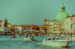 VENICE, ITALY - JUNE 18, 2015: The green dome of cathedral in Venice behind the grand canal. People using taxi boats.  stock photo