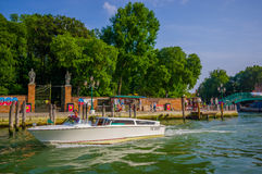 VENICE, ITALY - JUNE 18, 2015: Little bote sailing in Venice, summer day. At the bottom a nice shopping street Royalty Free Stock Image