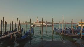 VENICE, ITALY - JUNE 19, 2016: Parking gandolas on the Doge's palace embankment with the bell tower of the Saint Giorgio stock video footage