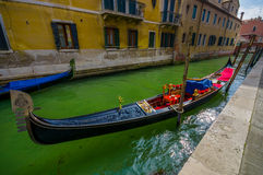 VENICE, ITALY - JUNE 18, 2015: Parking gondola in Venice canal, ready to be used. Water transporation Stock Photos