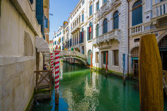 VENICE, ITALY - JUNE 18, 2015: Sun ray illuminating a beautiful historic house and white bridge, tourisit visitting Royalty Free Stock Photos