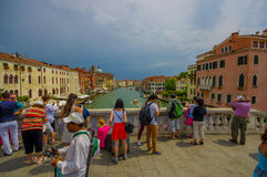 VENICE, ITALY - JUNE 18, 2015: Tourists of all the world arrives to Venice, nice bridge on grand canal. Romantic old Stock Images