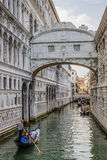 Venice, Italy - June 27, 2014: Tourists sailing on gondolas  on water canal under Bridge of Sighs Royalty Free Stock Image