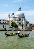 Venice, Italy - 15 June 2017 - Two Gondolas with People Enjoying Their Time in Venice and Basilica of Saint Mary of Health in the Stock Images