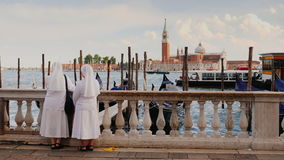 Venice, Italy, June 2017: Two nuns in white robes admire the beautiful view of Venice and the bay with ships and. Two nuns in white robes admire the beautiful stock video footage