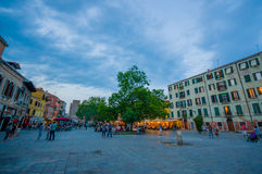 VENICE, ITALY - JUNE 18, 2015: Venetian sunset in a popular square, restaurants preparing everything. Nice tree in the Stock Photography