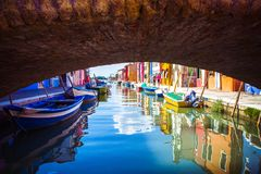 View under bridge of colorful Venetian houses and boats at Islands of Burano in Venice, Italy stock image