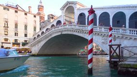 Water taxi goes under The Rialto Bridge in Venice. Venice, Italy - June 17, 2018: Water taxi goes under The Rialto Bridge in Venice stock footage