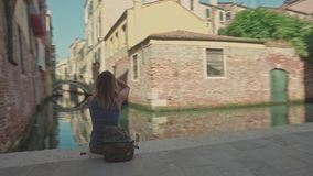 VENICE, ITALY - JUNE 19, 2016: Woman with a camera sitting on the embankment near small canal, Venice stock footage