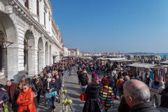 Venice, Italy large crowd at Venice Carnival. People walking on the waterfront of Venice ready to enter the main area of celebrations for the Venice 2017 Royalty Free Stock Photos