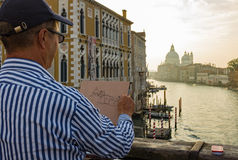 Venice,italy. Man drawing pictures The church of Santa Maria della Salute at Morning viewed from the bridge over the Grand Canal at Academia in the city of stock photos