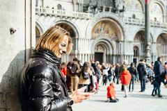 Masked man watching cell phone during Venetian carnival stock photos