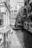 Venice, Italy - March 11, 2012: Typical Gondola with gondolier rowing along a narrow canal in Venice, black and white image stock photography