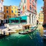 Venice, Italy - March 11, 2012: Typical venetian gondola with gondolier rowing along a narrow canal in Venice royalty free stock photo