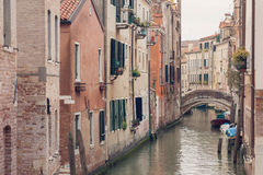 VENICE, ITALY - MARCH 17, 2016. Urban canal and boats on it, on a gloomy day in Venice, Italy. Vintage filter. Stock Images