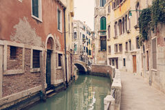 VENICE, ITALY - MARCH 17, 2016. Urban canal and boats on it, on a gloomy day in Venice, Italy. Vintage filter. Royalty Free Stock Images